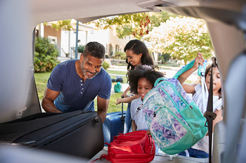 A photograph of a family loading luggage into a car. The photo is by Getty Images.