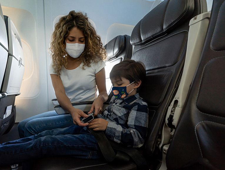Photo of mom and child with masks on a plane. Experts recommend avoiding the aisle seat, keeping masks on the entire flight, and sitting near the back of the plane. (Photo credit: Getty Images)