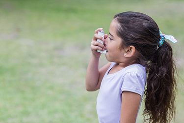 A young girl uses an inhaler to treat asthma. (Photo by Getty Images.)