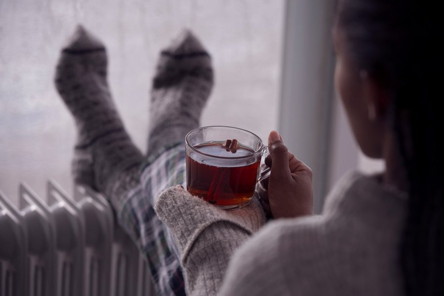 Photo of woman with socks and warm drink trying to warm up. (Photo credit: Getty Images)