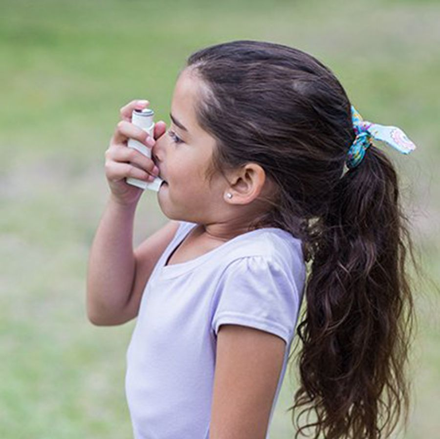 A young girl uses an inhaler. (Photo by Getty Images)