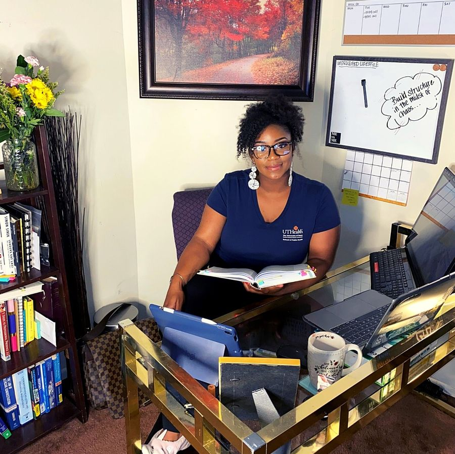 Bri sits in her home office, surrounded by books.