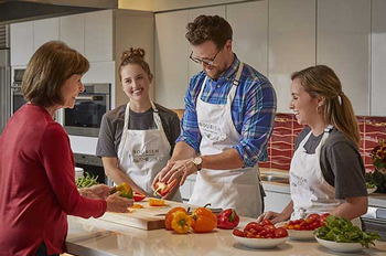 Photo of Wesley McWhorter, MS, RD, preparing food with Laura Moore, MEd, RD, and students watching (Photo by Terry Vine)